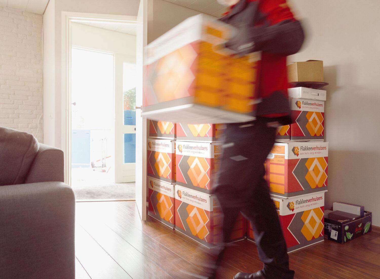 Een verhuizer draagt alle verhuisdozen naar de vrachtwagen